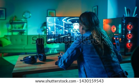 Back Shot of a Gamer Girl Playing First-Person Shooter Online Video Game on Her Powerful Personal Computer. Room and PC have Colorful Warm Neon Led Lights. Cozy Evening at Home.