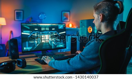 Back Shot of a Gamer Playing First-Person Shooter Online Video Game on His Powerful Personal Computer. Room and PC have Warm Colorful Neon Led Lights. Cozy Evening at Home.