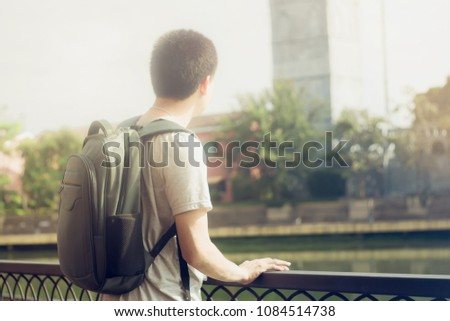Back shot of young man traveler with backpack relaxing outdoor look at tourist attraction. Tourist stand on lake side looks at other side of lake. #1084514738