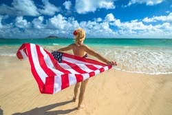Back side Hawaiian woman holding a waving American flag in American flagged bikini. Tropical Lanikai Beach, east shore of Oahu in Hawaii, USA. Freedom and 4th July patriotic concept.