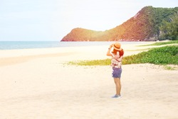 Back side of a alone traveller woman sitting in font of the beautiful sea sand beach in Thailand, Holliday or summer vacation trip relaxing and backpack travel