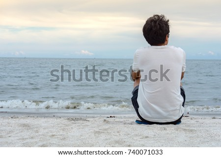 Back side of Asian man in white shirt, sitting and waiting or thinking about something, in feeling lonely sadness. at the beach sea and blue sky.