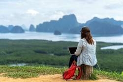 Back side of Asian woman freelancer working with technology laptop with happiness action at Fantastic Landscape of samed nang chee view point, Freelance working and travel anywhere concept