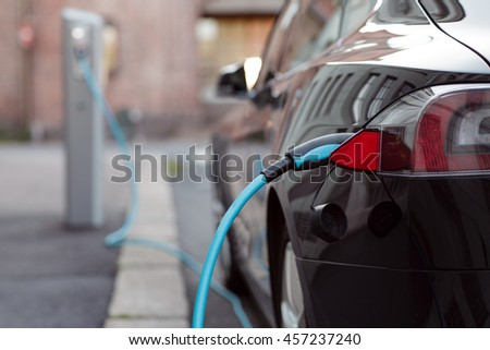 Back side of the car loading energy. Detail of the power supplier for charging of an electric car.
