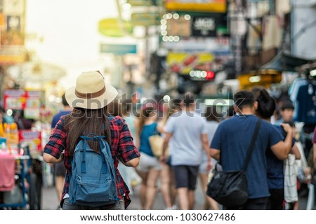 Back side of Young Asian traveling women walking and looking in Khaosan Road walking street in evening at Bangkok, Thailand, traveler and tourist concept #1030627486