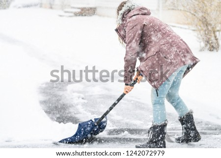 Back, side of young woman, female in winter coat cleaning, shoveling driveway, street from snow in heavy snowing snowstorm, holding shovel, residential houses