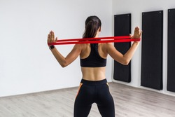 Back side portrait of sporty woman wearing in black top and leggings performs exercises for the muscles of back and hands, workout with resistance band on white background. Indoor home workout concept
