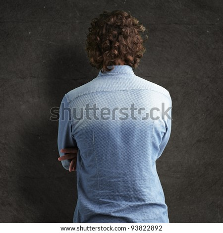 Back side view of a man against a grunge wall