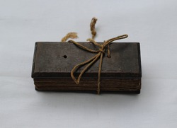 Back side view of a old book which is full with ancient Palm leaf manuscripts bind together by thick rope