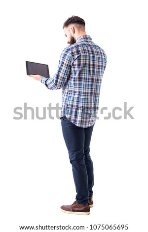 Back side view of young business man using and working on tablet computer. Full body length isolated on white background.