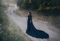 back silhouette gothic lady old fantasy horror movie. woman Walks along  road in autumn forest. Beautiful queen vampire. Black vintage dress long train. design Old dark fashion. Halloween holiday