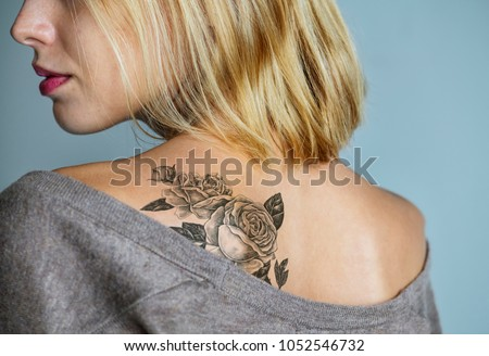 Back tattoo of a woman - Shutterstock ID 1052546732