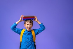Back to school! A cheerful schoolboy against a purple paper wall. A child with a backpack, books and notebooks. The boy is ready to study.