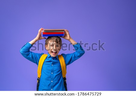 Back to school! A cheerful schoolboy against a purple paper wall. A child with a backpack, books and notebooks. The boy is ready to study. Stock photo ©