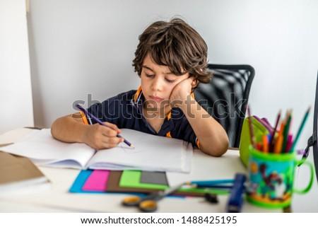 Back to school. A little boy is doing homework.