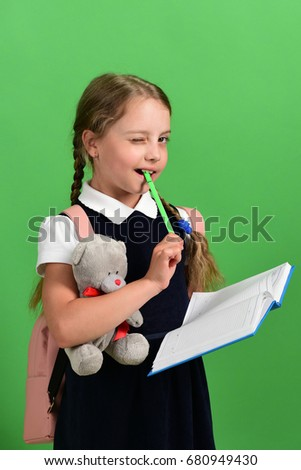 Back to school and education concept. Girl holds teddy bear, open notebook and green marker. School girl with flirty smile isolated on green background. Pupil in school uniform with braids and bag