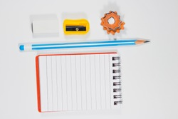 Back to school and education minimal concept with pencil, eraser, sharpner, notebook and wooden pencil shavings on a white background
