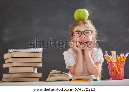 Back to school and happy time! Cute industrious child is sitting at a desk indoors. Kid is learning in class on background of blackboard. Girl reading the book. #674372218