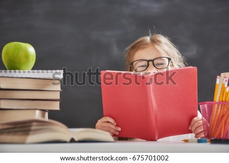 Shutterstock Back to school and happy time! Cute industrious child is sitting at a desk indoors. Kid is learning in class on background of blackboard. Girl reading the book.