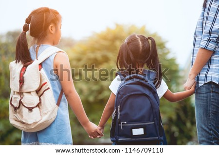 Back to school. Asian mother and daughter pupil girl with backpack holding hand and going to school together in vintage color tone #1146709118