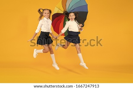 Back to school at any weather. Little girls of primary school age smiling under colorful umbrella on yellow background. Happy small children hurry to school. Enjoying school holidays in autumn. Stock photo ©