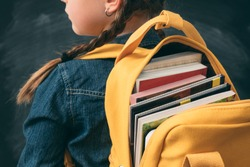 Back to school. Back view of young girl ready to study, with open backpack full with books.