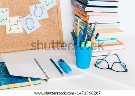 Back to school background. Stationery accessories – notebooks piles, plastic holder pencils, pens, markers, stickers, notepads, glasses and corkboard with stack of books education concept