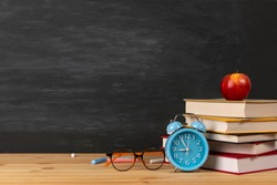 Back to school background with books, alarm clock, eyeglass and apple over chalkboard.