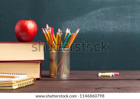 Back to school background with books and apple over blackboard - Shutterstock ID 1146860798