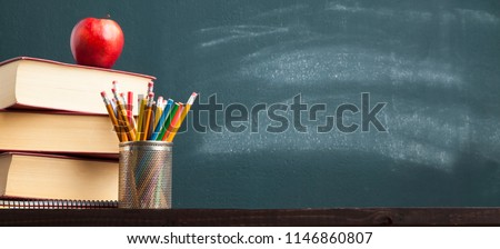 Back to school background with books and apple over blackboard - Shutterstock ID 1146860807