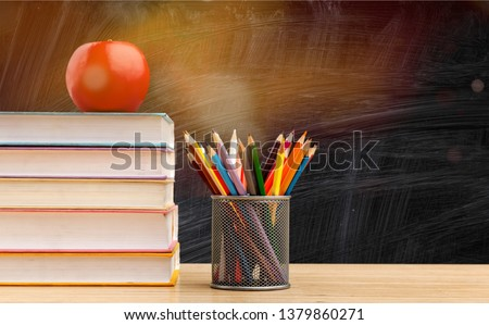 Back to school background with books and apple over blackboard #1379860271