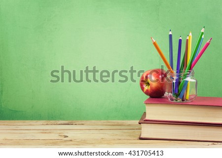 Back to school background with books, color pencils and apple over green wallpaper