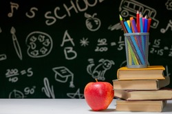 Back to school background with books, pencils and apple on white table