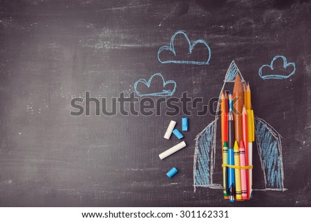 Back to school background with rocket made from pencils. View from above