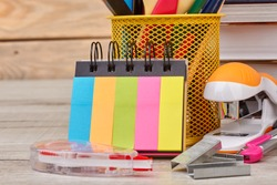 Back to school background with various school supplies. Holder with colored pencils, books, binder notepad, stapler, divider and other stationery accessories.