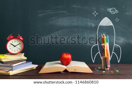 Back to school banner. Rocket sketch and open book in front of blackboard - Shutterstock ID 1146860810