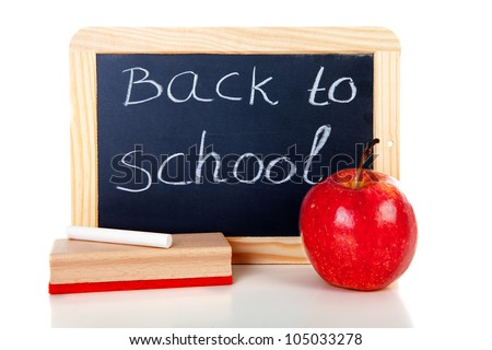 back to school: blackboard slate, wiper, chalk and apple over white background