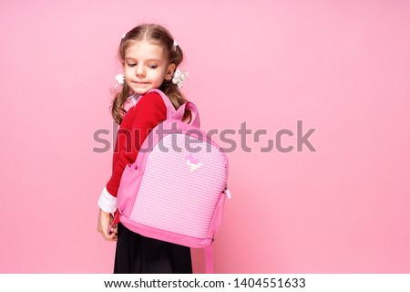 Back to school. Child with schoolbag. Schoolgirl 7-8 years old in a red jacket, white shirt, pigtails, black sarfan, school uniform with school bag isolated on pink