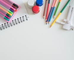 Back to school concept and artist kid concept with Drawing book, crayons, coloured pencils, Poster color and School stationery on white wooden background with copy space