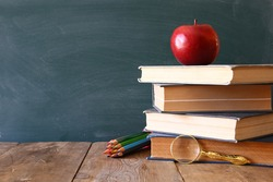 Back to school concept. Blackboard with books and apple on wooden desk