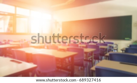 Back to school concept. Classroom in blur background without young student; Blurry view of elementary class room no kid or teacher with chairs and tables in campus.