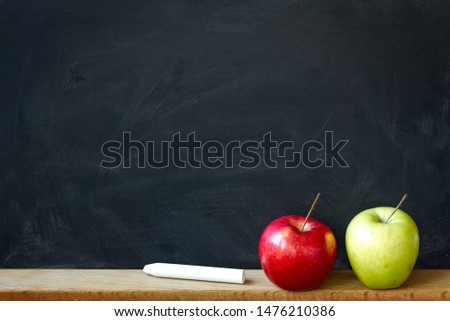 Back to school concept, closeup black chalk board in chalk stains chalk board and two apples red and green, selective focus, copyspace
