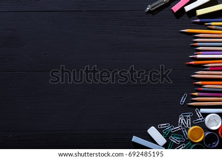 Back to school concept, colorful pencils on black art table, multicolored stationery supplies for teaching kids drawing on empty dark wooden desk, creative education background, top view, copy space