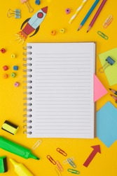 Back to school concept. Colorful rocket, open notebook, school supplies. Yellow background. Flat lay, copy space.