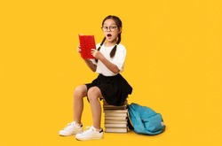 Back-To-School Concept. Cute Elementary School Girl Reading Book Sitting On Books Stack Over Yellow Studio Background.