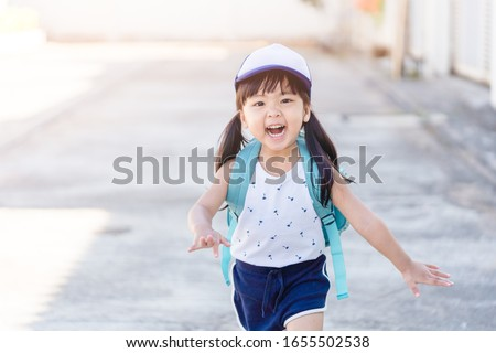 Back to School Concept.Happy Funny little asian girl running and very excited and glad when she go back to school.Happy toddler child from kindergarten school.School kid girl with japan bag.Education.