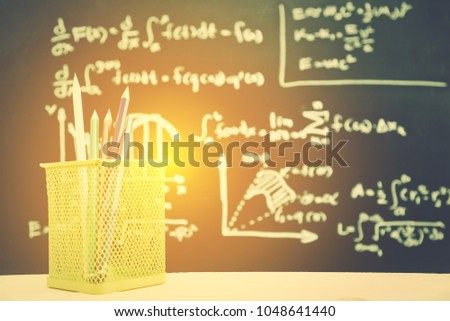Back to school concept : Pencils in a square box near a blackboard or chalk board with math / calculus formular or arithmetic operations / equations e.g differential equation and the definite integral