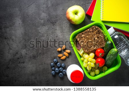 Back to school concept. School and office stationery, backpack and lunch box on black background. Top view.