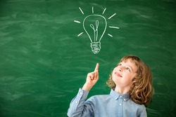 Back to school concept. School child in class. Smart kid against green blackboard. Schoolchild drawing light bulb on chalkboard. Idea and creativity concept. Copy space for your text
