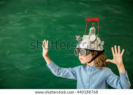 Back to school concept. School child with virtual reality headset. Kid in class. Nerd child in classroom. Funny geek kid against green blackboard. Innovation technology and education concept